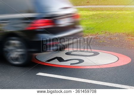 A Moving Car In Violation Of Traffic Rules, Limiting The Maximum Speed To 30.