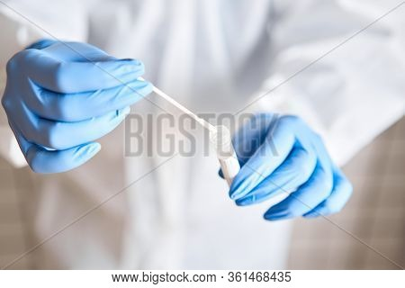 Doctor Holding Swab Test Tube For 2019-ncov Analyzing. Coronavirus Test. Blue Medical Gloves And Pro