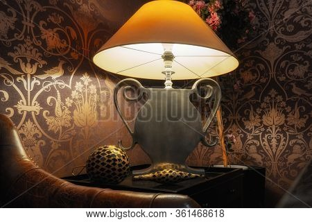 Yellow Shade, Silver Foot Lamp In Vintage Environment With Leather Sofa In Front