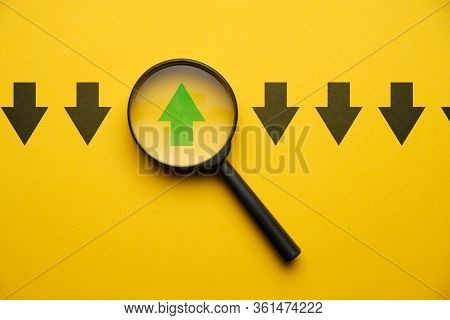 Abstract Arrow In A Magnifier On A Yellow Background - Concept Think Differerntly. Close Up.