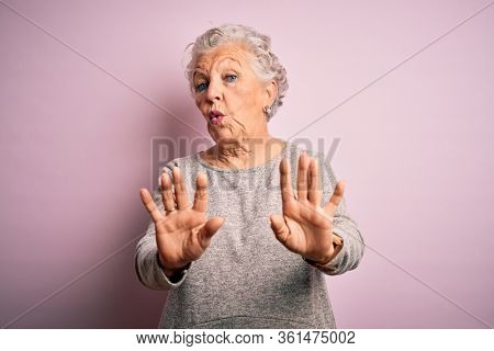 Senior beautiful woman wearing casual t-shirt standing over isolated pink background Moving away hands palms showing refusal and denial with afraid and disgusting expression. Stop and forbidden.