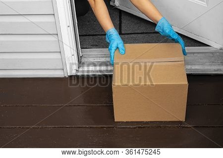 A Person Wearing Gloves, Picking Up A Deliver Box From A Home Entrance
