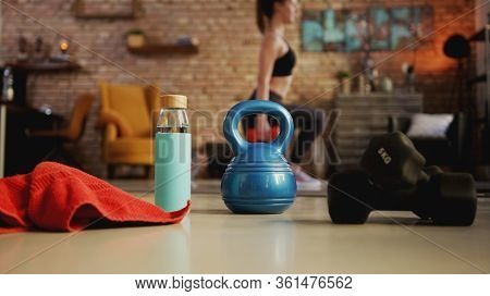 Fitness training at home. Young woman doing leg workout, exercising in living room. Focus on fitness equipment. Stay at home and stay fit and healthy.