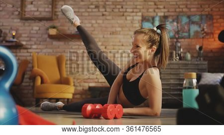 Fitness training at home. Young woman doing leg workout, exercising in living room. Stay at home and stay fit and healthy.