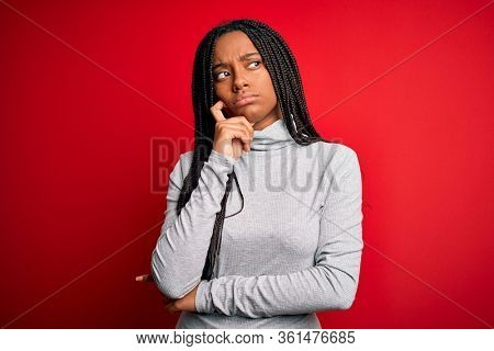 Young african american woman wearing turtleneck sweater over red isolated background with hand on chin thinking about question, pensive expression. Smiling with thoughtful face. Doubt concept.