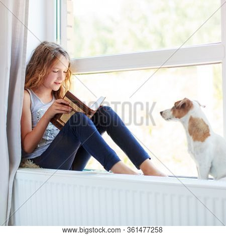 Child reading book at home. Girl sitting at window at read