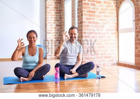 Middle age sporty couple sitting on mat doing stretching yoga exercise at gym smiling positive doing ok sign with hand and fingers. Successful expression.