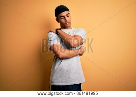 Handsome african american sportsman doing sport wearing sportswear over yellow background Hugging oneself happy and positive, smiling confident. Self love and self care