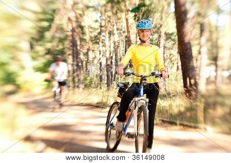 Couple On Bikes In The Sunny Forest