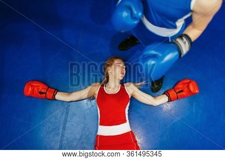 Women boxing, girl in red is knocked out
