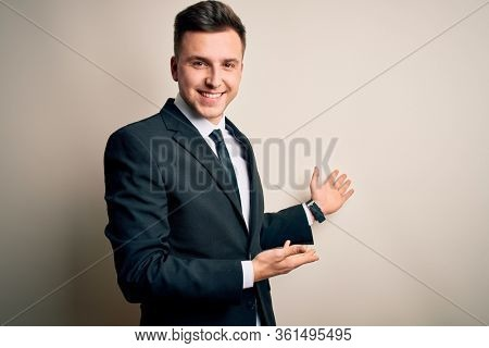 Young handsome business man wearing elegant suit and tie over isolated background Inviting to enter smiling natural with open hand