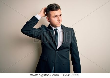 Young handsome business man wearing elegant suit and tie over isolated background confuse and wondering about question. Uncertain with doubt, thinking with hand on head. Pensive concept.