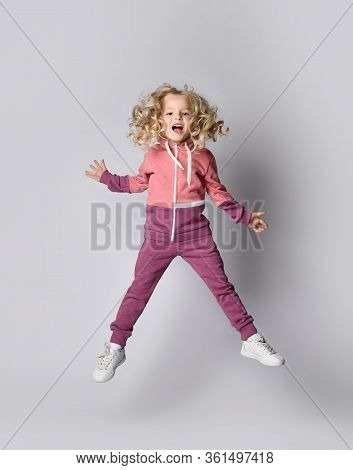 Full-growth Portrait Of Playful Frolic Kid Girl In Stylish Modern Pink Gray Sport Suit Hoodie And Pa