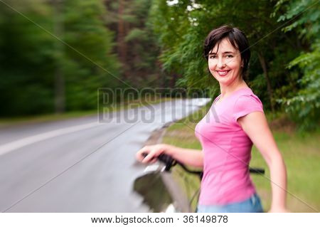 Woman With Bike On The Rainy Forest Road. Lensbaby Effect