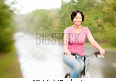 Woman Riding Bike On The Rainy Forest Road. Lensbaby Effect