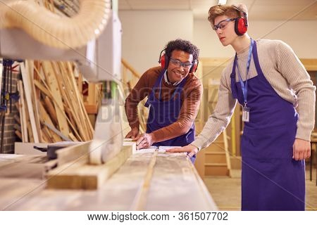 Tutor With Male Carpentry Student In Workshop Studying For Apprenticeship At College Using Bench Saw