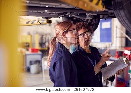 Female Tutor With Student Looking Underneath Car On Hydraulic Ramp On Auto Mechanic Course