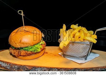 A Crispy Breaded Chicken Burger Served Alongside A Portion Of French Fries