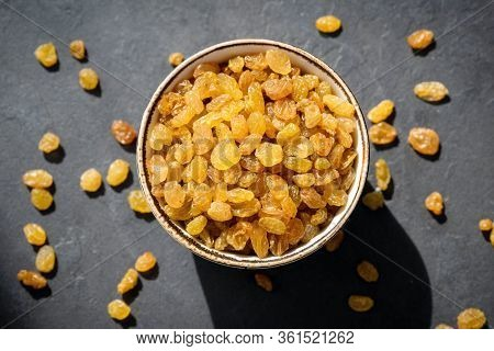 Golden Raisins Or Sultana In Bowl On Black Background, Table Top View. Dried Fruit, Healthy Snack Fo