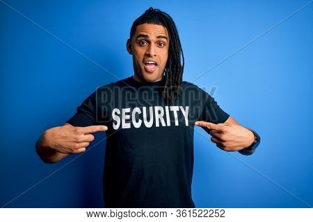 Young african american afro safeguard man with dreadlocks wearing security uniform very happy pointing with hand and finger