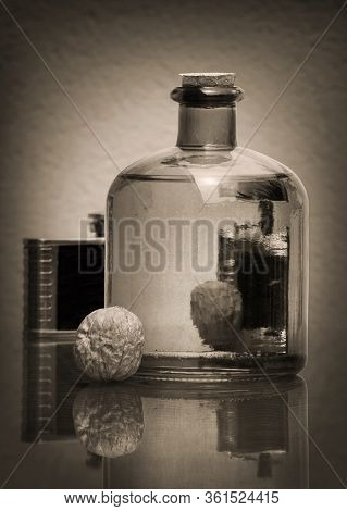 Still Life In Sepia Tone With Transparent Glass Bottle, Black Vintage Hip Flask, And Walnuts Against