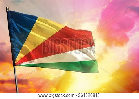 Fluttering Seychelles Flag On Beautiful Colorful Sunset Or Sunrise Background. Seychelles Success An