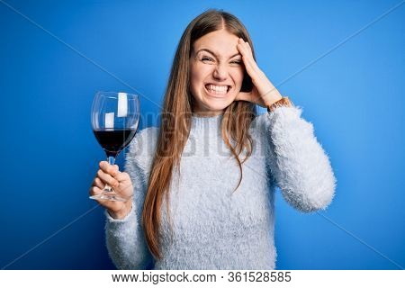 Young beautiful redhead woman drinking glass of red wine over isolated blue background stressed with hand on head, shocked with shame and surprise face, angry and frustrated. Fear and upset