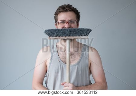 Young Man Standing Ready For Cleaning Floor With Mop