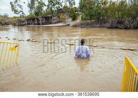 QASR El-YAHUD, ISRAEL - MARCH 2, 2020: Young man in baptismal shirt enters the water of the Jordan River. Baptism ceremony. The site of the baptism of Jesus Christ. The concept of pilgrimage