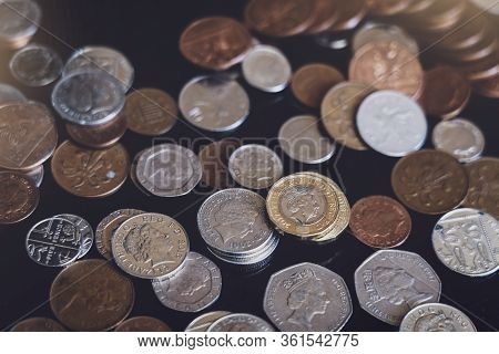 Top View New One Pound Sterling Coin And Penny On Black Background, Pile Of Different British Money