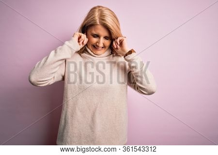 Middle age beautiful blonde woman wearing casual turtleneck sweater over pink background covering ears with fingers with annoyed expression for the noise of loud music. Deaf concept.