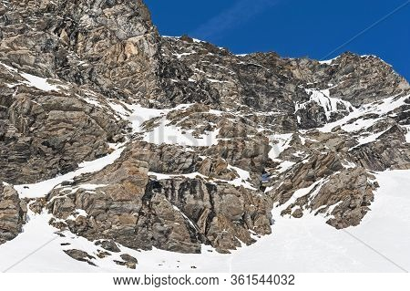 Rugged Alpine Rocky Mountainside Landscape With Frozen Waterfall Covered In Snow And Ice