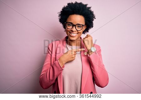 Young beautiful African American afro businesswoman with curly hair wearing pink jacket In hurry pointing to watch time, impatience, looking at the camera with relaxed expression
