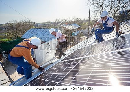 Male Team Workers Installing Solar Photovoltaic Panel System. Electricians Lifting Blue Solar Module