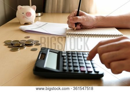Blurred Selective Focus, Male Hand With Piggy Bank Calculating On Financial, Tax And Business Financ