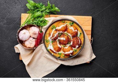 Malai Kofta Curry In Black Bowl At Dark Slate Background. Malai Kofta Is Indian Cuisine Dish With Po