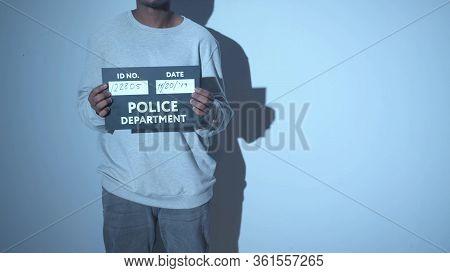 A Criminal Is Being Photographed. Mugshot Sign