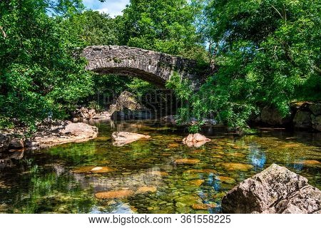 Doctor Bridge On A Summer Afternoon: A Packhorse Bridge Over The River Esk Near Eskdale, Lake Distri