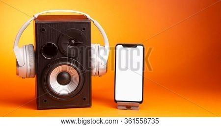 White headphones on speaker and smartphone, music online concept, mockup, isolate on orange