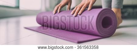 Yoga at home woman rolling pink exercise mat in living room starting warm up meditation zen well being wellness banner panoramic apartment living room lifestyle.