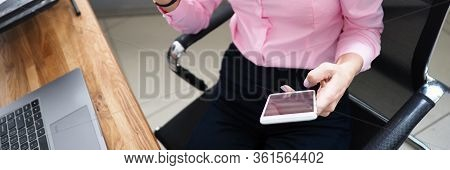 Woman In Office Shows Bank Card And Calls By Phone. Order Goods And Services Online With Ability To