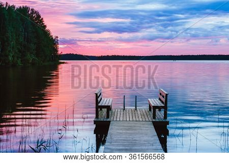 Two Wooden Chairs Bench On A Wood Pier Overlooking A Lake At Sunset