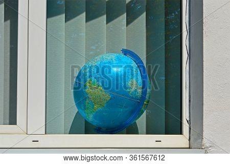 Kamenets-podolsky, Ukraine - Aug 25, 2019: Blue Globe In The Window With White Jalousie Aka Blinds O