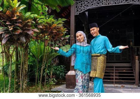 Young Couple Of Malay Muslim In Traditional Costume During Aidilfitri Celebration Showing Welcome Gr