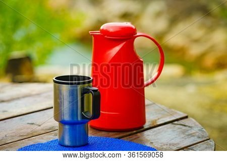 Picnic Site Table With Thermos And Thermal Mug, Norwegian Mountains Nature In The Background. Campin