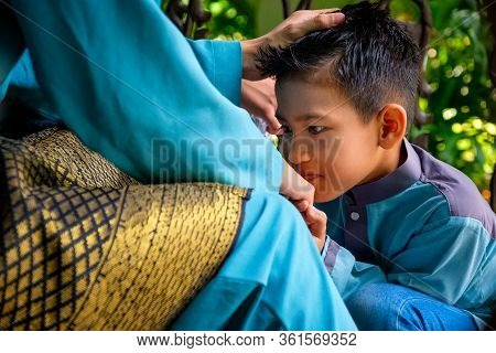 Closeup Of Malay Muslim Son In Traditional Costume Showing Apologize Gesture To His Parent During Ai