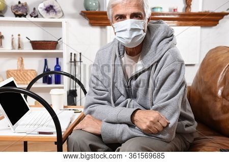 Man not feeling well wearing a COVID-19 face mask while working from home.