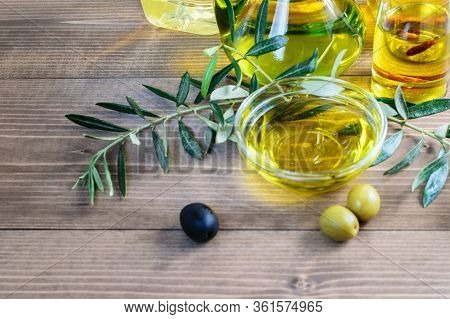 Assortment Of Olive Oil Bottles, Olive Oil In Glass Transparent Bowl And Some Olives And Leaves On T