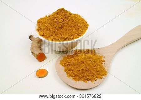 Turmeric Powder In A White Cup And Turmeric Root Isolated On A White Background. Used As A Tonic For