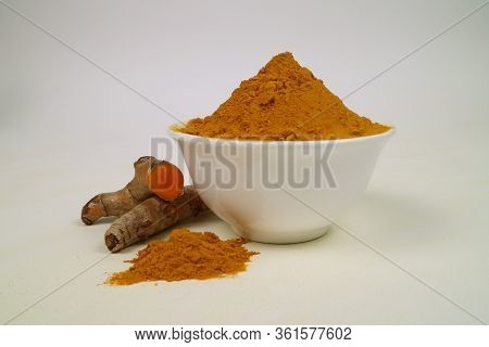 Turmeric Powder In A White Cup And A Separate Turmeric Root On A White Background Is Used As A Tonic